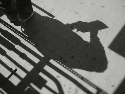 The shadow of a J train rider on the platform of the Marcy Street subway station in Williamsburg, Brooklyn. Photographed by Michael Pinto on May 21st, 2007.