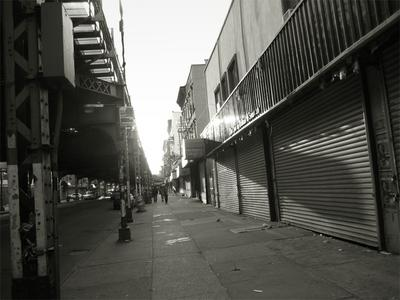 The sun setting on Broadway in Williamsburg, Brooklyn near the entrance to the Hewes subway station. Photographed by Michael Pinto on May 20th, 2007.